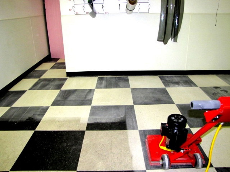 VCT Cleaning without the mess - dry process. This is an automotive shop floor with lots of tire marks and greasy dirt.